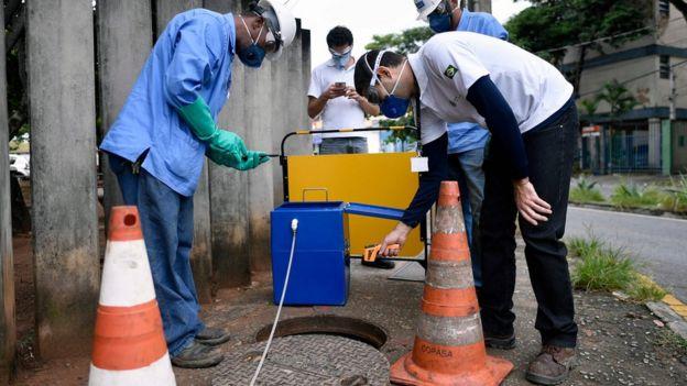 Técnicos tomando pruebas de una alcantarilla en Belo Horizonte, Brasil