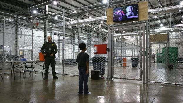 A child detainee watches a movie