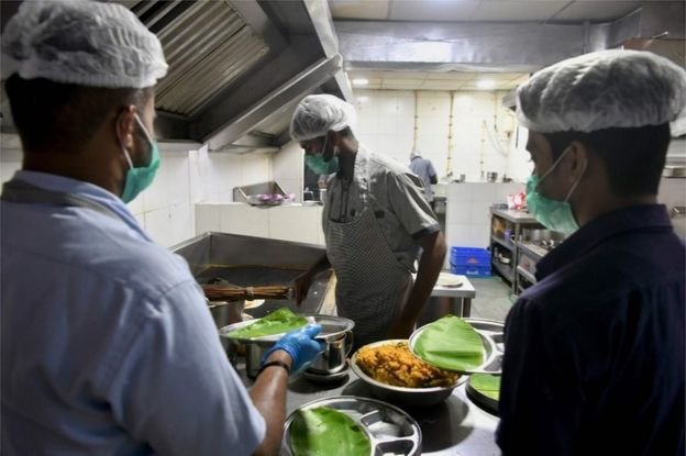 Staff members of the Indian Railway Catering and Tourism Corporation (IRCTC) wear facemasks, as a preventive measure againsts the spread of the COVID-19 coronavirus outbreak, as they prepare food for customers in a restaurant at Bangalore City Railway Station, on March 4, 2020