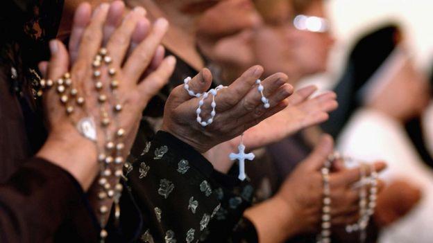 Personas rezando con rosarios.