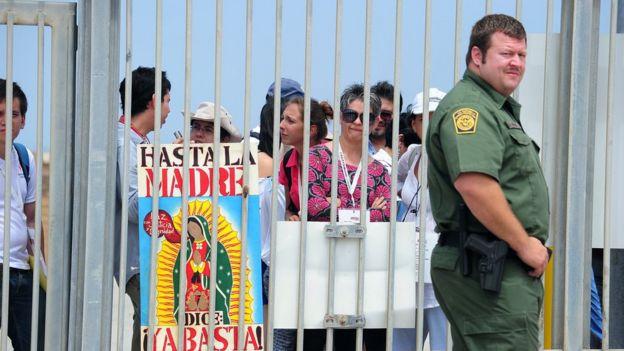 Un guardia fronterizo de EE.UU., junto a mexicanos que protestan en San Diego, California.