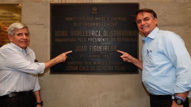 O ministro do Gabinete de Segurança Institucional (GSI), general Augusto Heleno, e o presidente Jair Bolsonaro posam para foto com placa com o nome do ex-presidente militar João Figueiredo