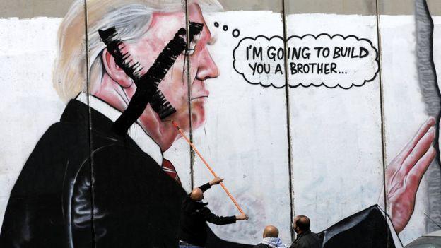 Filistinliler İsrail'in inşa ettiği duvardaki Trump resminin yüzünü boyuyor. Resimde, Meksika sınırına duvar inşa etmek isteyen Trump'ın kafasından
