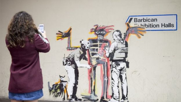 A woman takes a photo of one of two new murals painted by the artist Banksy near the Barbican Centre