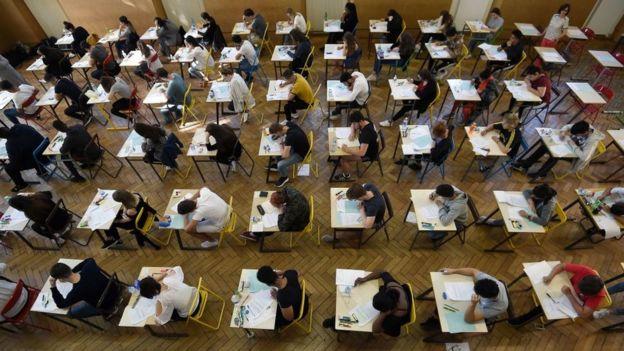Alumnos en un salón realizando una prueba.