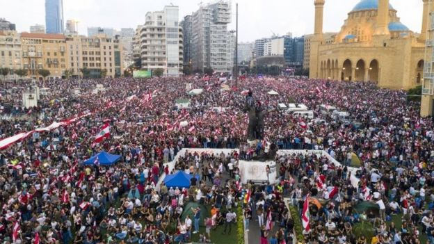 A picture taken with a drone shows an aerial view for protesters wave Lebanese flags and shout anti-government slogans during a protest in front of Muhammad al-Amin Mosque in downtown Beirut, Lebanon, 20 October 2019.