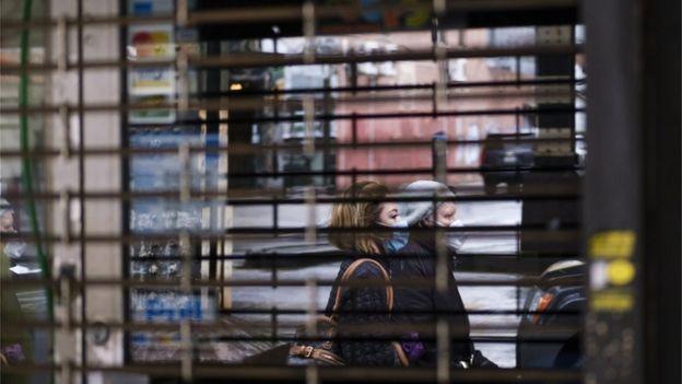 Duas pedestres com máscara passam em frente a comércio fechado com grades em Nova York