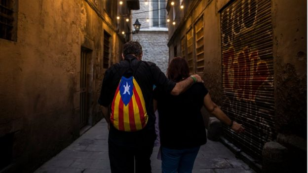 A man wears a backpack showing the Catalan separatist flag as he walks at El Born district in Barcelona, October 11, 2017