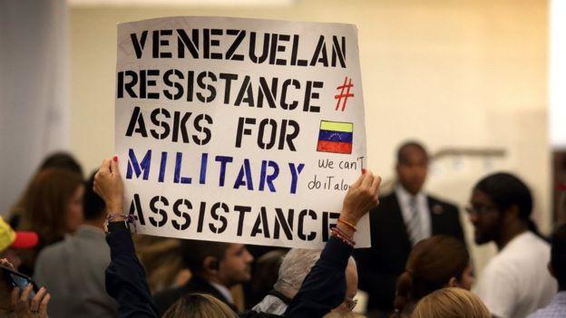 Una mujer sostiene un cartel en la reunión de venezolanos con Mike Pence