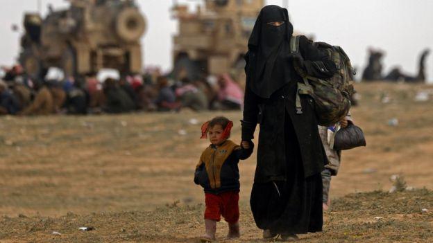 Mulher e criança deixam área controlada pelo EI em fevereiro de 2019