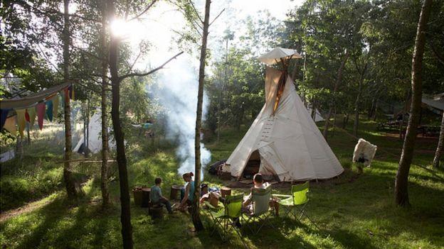 Crianças sentadas ao ar livre, próximas a uma tenda