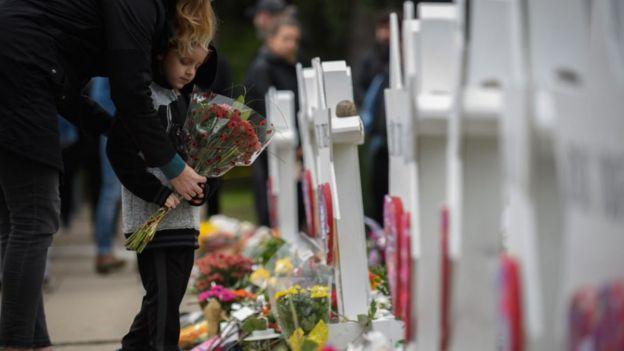 Niño colocando flores en memorial de muertos por tiroteo