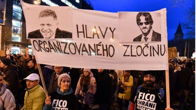 """Người dân Slovakia mang theo biểu ngữ """"những kẻ đứng đầu tội phạm có tổ chức"""" cùng với hình Thủ tướng Robert Fico và Bộ trưởng Nội vụ Robert Kalinak"""