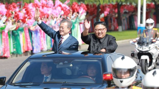 This picture taken on September 18, 2018 and released by Korean Central News Agency (KCNA) via KNS shows North Korean leader Kim Jong Un (R) and South Korean President Moon Jae-in (L) waving to Pyongyang citizens from an open-topped vehicle as they drive through Pyongyang.