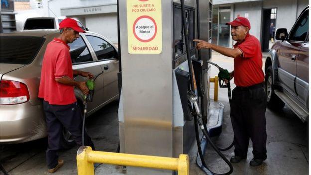 Imagem mostra dois frentistas em um posto de combustíveis da Venezuela no momento em que operam as bombas de abatecimento de veículos