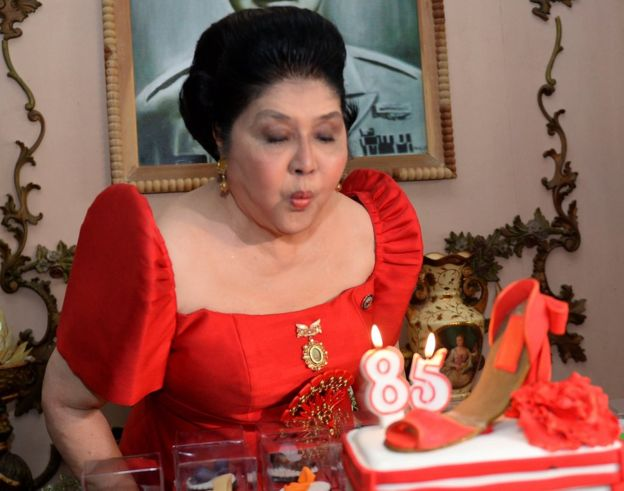 Former Philippines first lady and now congresswoman Imelda Marcos blows out the candles on a cake designed with a shoe during her 85th birthday celebrations