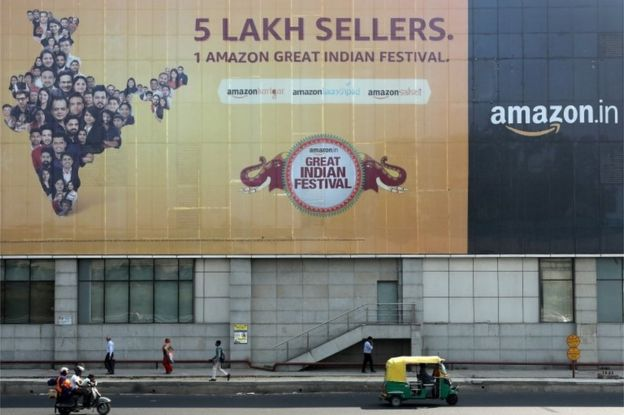 People move past a hoarding of Amazon India outside a metro rail station in New Delhi, India, October 23, 2019
