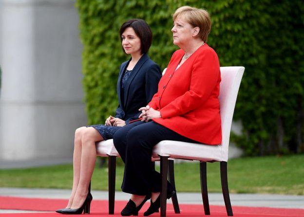 La canciller de Alemania, Ángela Merkel (der.) y la primera ministra de Moldavia, Maia Sandu, sentadas escuchando los himnos nacionales durante una recepción en Berlín, 16 de julio de 2019