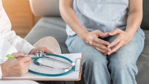 Mulher sentada conversando com médico