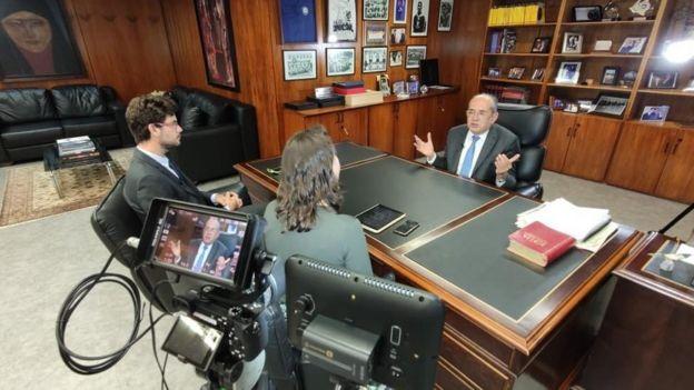 Em seu gabinete, Gilmar Mendes conversa com dois repórteres da BBC, todos filmados por câmera