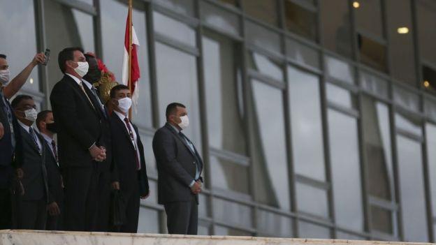 Bolsonaro, de máscara, rodeado por assessores na rampa do Planalto