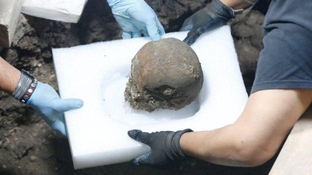Dos investigadores cargan uno de los cráneos.