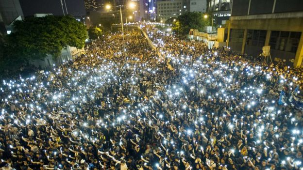 Protesters and student protesters wave their cell phones in solidarity during a protest outside the Legislative Council headquarters in Hong Kong on September 29, 2014