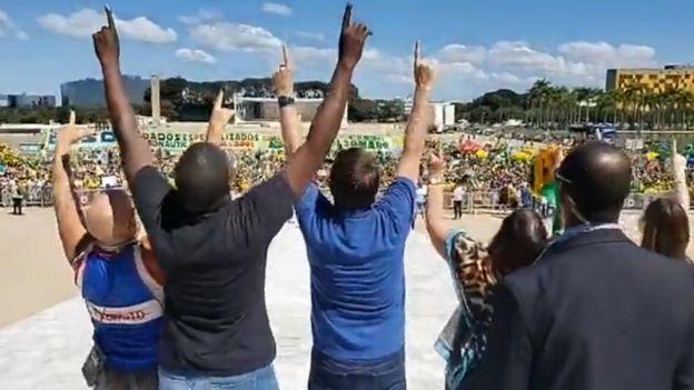 Bolsonaro junto com os apoiadores apoiando os dedos para o céu