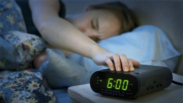 mulher na cama com a mão no relógio