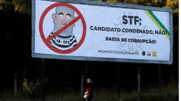 Mulher passa por outdoor com ilustração de Lula vestido de presidiário e mensagem ao STF 'Candidato condenado não'