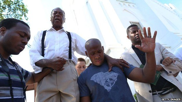 Rev Franklin Ferguson (2nd L) and Pastor Philip Pinckney (2nd R) join together to lead a group prayer in front of the Emanuel African Methodist Episcopal Church on 20 June 2015 in Charleston, South Carolina