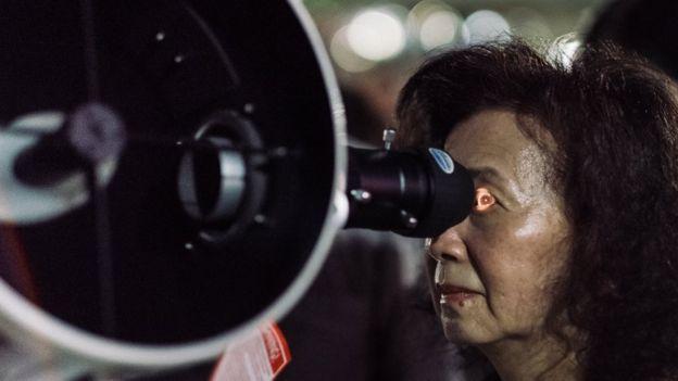 Mujer viendo el eclipse lunar a través de un telescopio en Taiwán.
