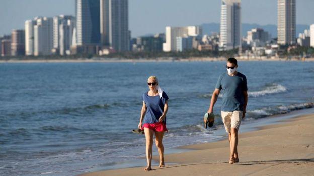 Dos personas caminan por una playa en Da Nang, Vietnam.