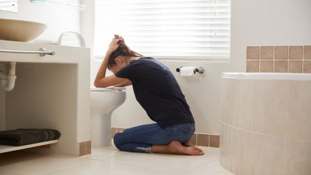 Mujer vomitando.