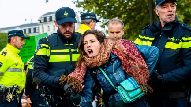 A woman is arrested by police at a protest in Amsterdam