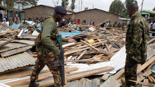 Police officers stand on the debris of a collapsed school classroom