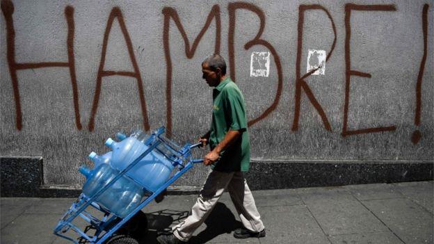 Hombre camina en Venezuela con botellones de agua vacíos frente a una inscripción que dice: Hambre.