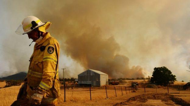 一名乡村消防局消防员于2020年1月11日在澳大利亚图姆巴伦巴观看了一场大火