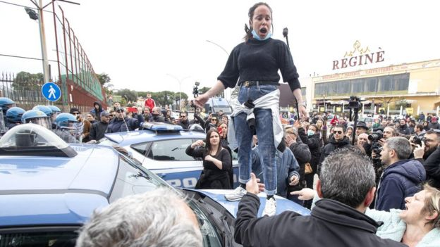 Relatives of inmates protest as law enforcement officers stand outside the Rebibbia prison in Rome, where a riot earlier broke out, 9 March 2020