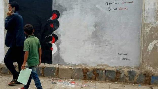الجدارية تشرح الدمار الذي حدث ولازال يحدث في اليمن وتصور الجدارية امرأة وطفل بتابعون ما خلفته الحرب