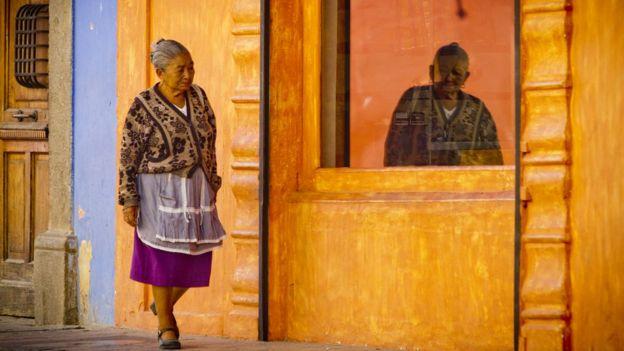 Mulher indígena caminha no centro histórico de Antigua, na Guatemala
