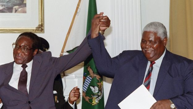 Zimbabwe's President Robert Mugabe (L) and former President of Zimbabwe African People's Union (ZAPU) Joshua Nkomo raise their fists 22 December 1987 in Nairobi.
