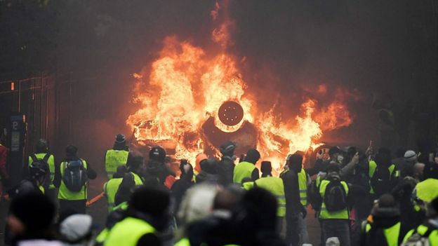 Demonstrators stand in front of a burning car during a protest of Yellow vests (Gilets jaunes)