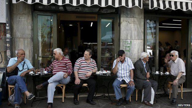Men sit outside cafe in Athens