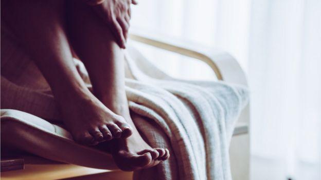 manos y pies de una mujer en su cama
