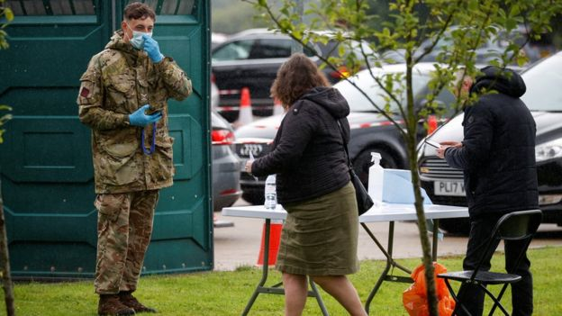 People and a soldier wearing a protective mask are seen at the coronavirus disease (COVID-19) testing center, as Blackburn with Darwen Council imposes local restrictions in an effort to avoid a local lockdown being forced upon the area, amid the coronavirus disease (COVID-19) outbreak, in Blackburn
