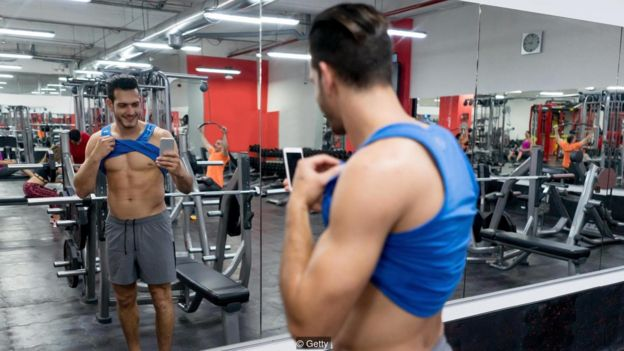 Hmem faz selfie com a camisa levantada em frente a espelho em uma academia