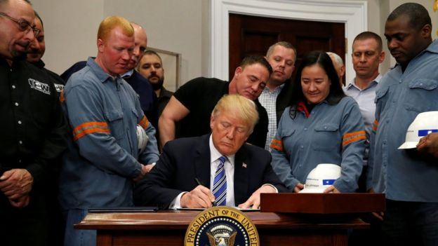 U.S. President Donald Trump signs a presidential proclamation placing tariffs on steel and aluminium imports while surrounded by workers from the steel and aluminium industries at the White House in Washington, U.S. March 8, 2018.