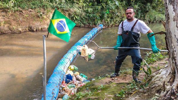 Diego em pé segurando uma rede cheia de lixo que retirou da barreira ecológica