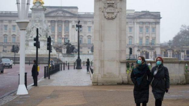 امرأتان ترتديان كمامة أمام قصر باكنغهام